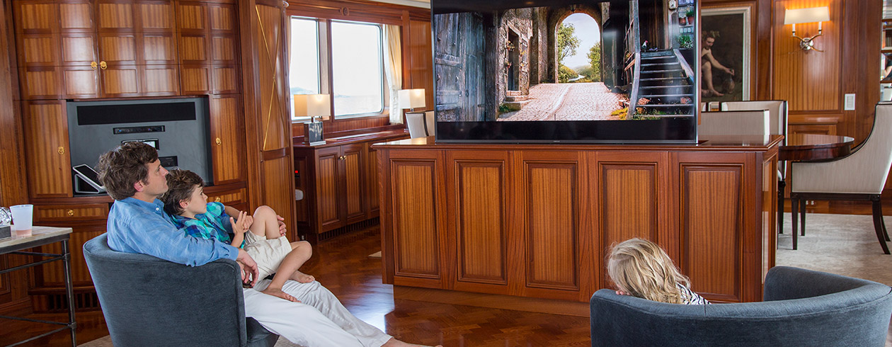 Family watching TV on superyacht
